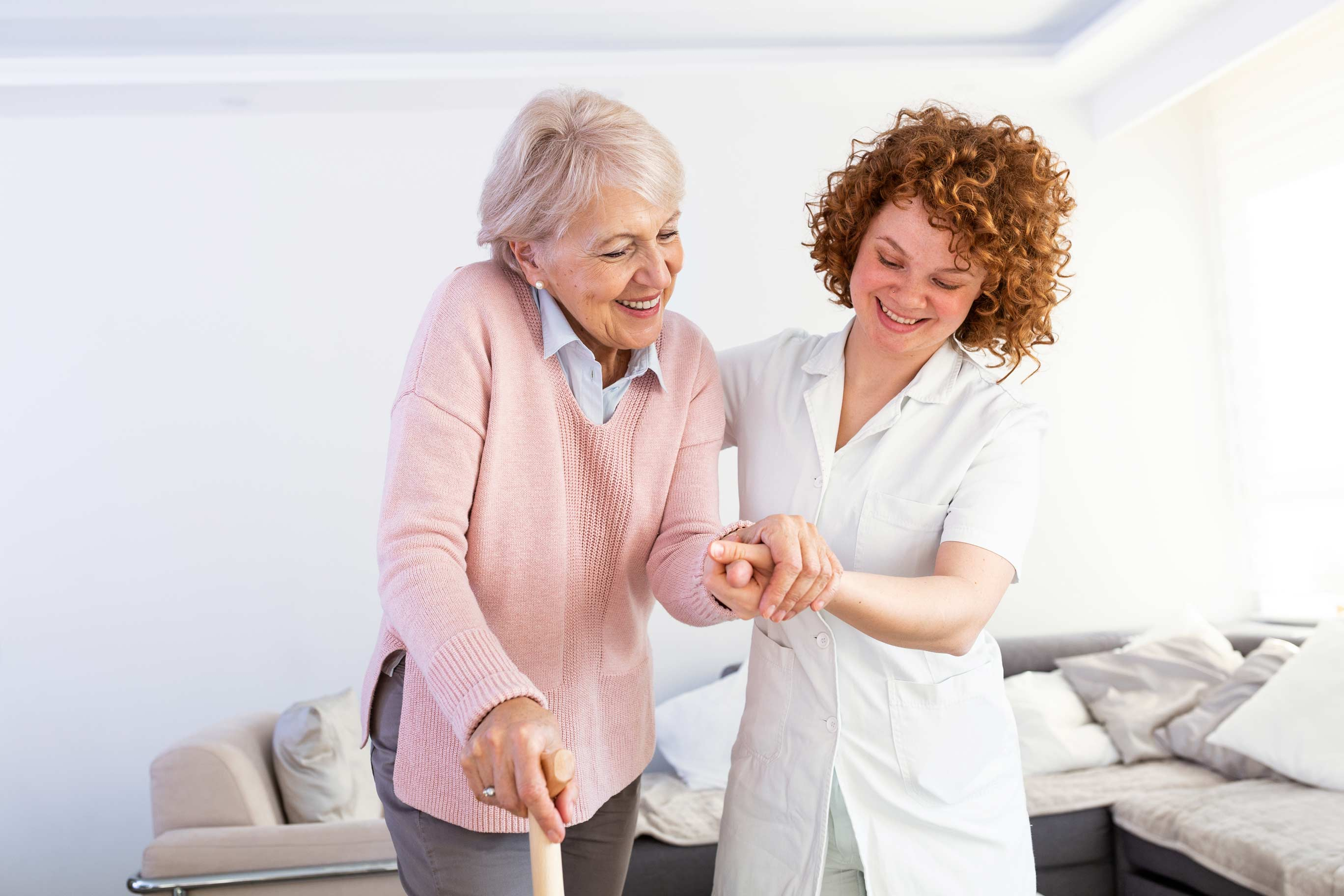 Carer helping support an elderly lady