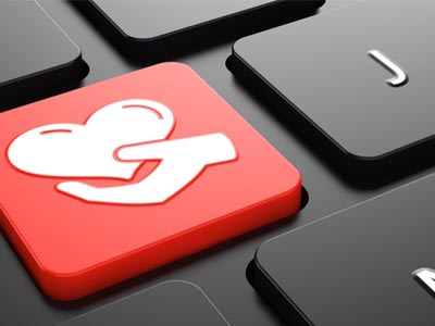 A keyboard with a red button with a heart in a hand