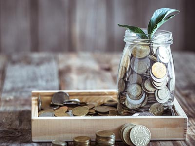 A plant growing out of a glass jar filled with coins