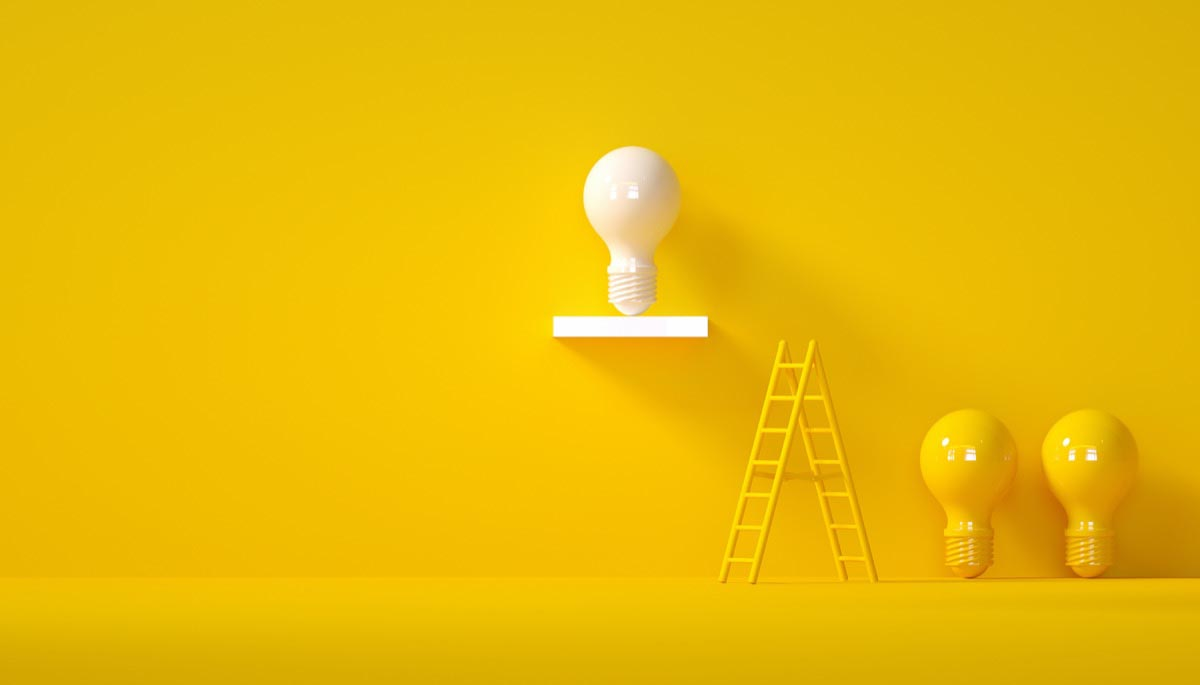 A lit lightbulb rising above yellow lightbulbs
