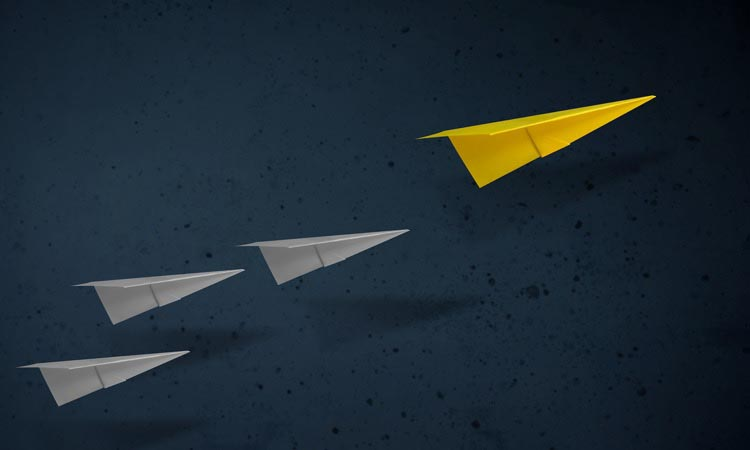 Four paper airplanes, the lead one is yellow