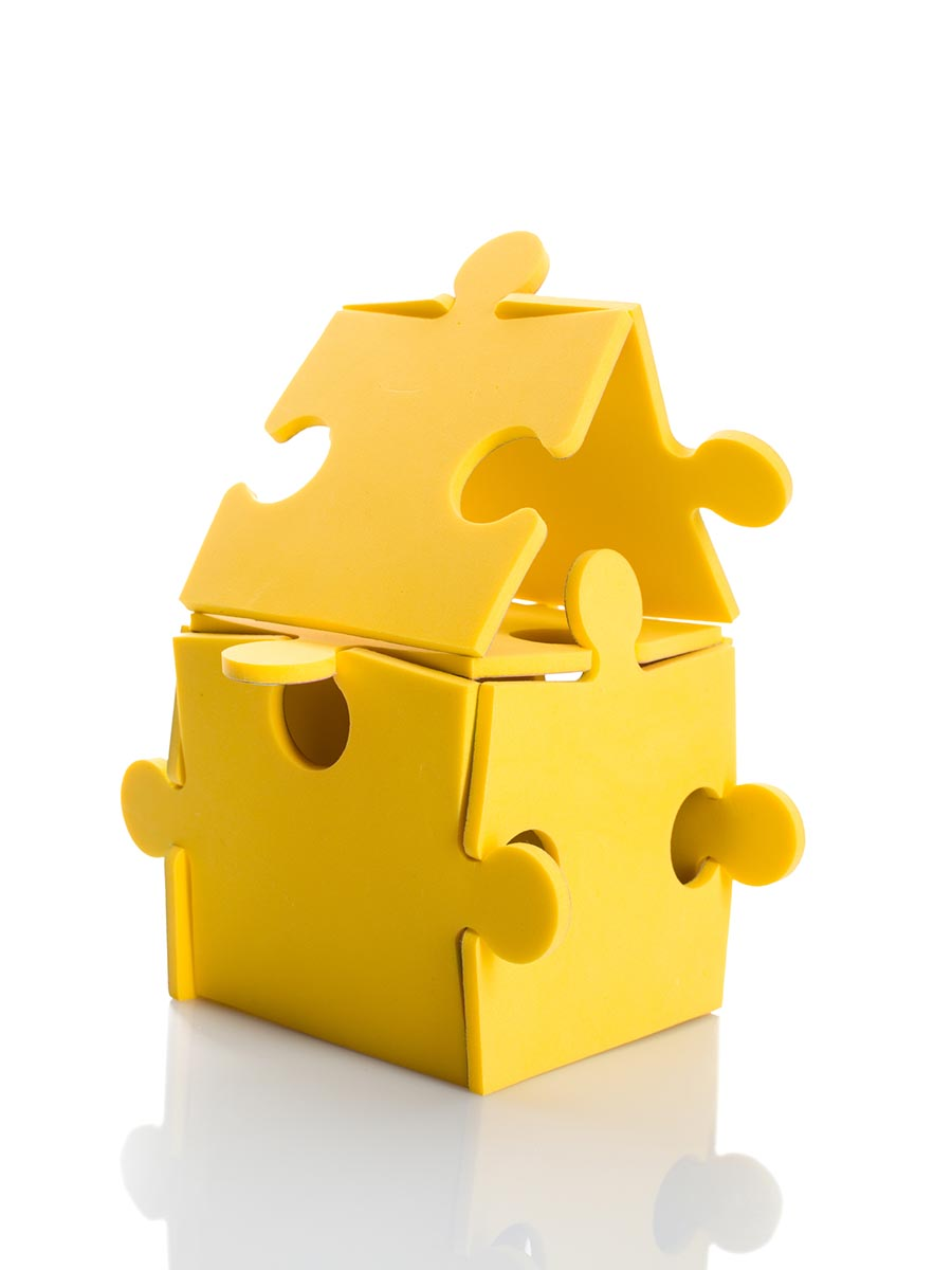 Yellow puzzle pieces forming a 3D house