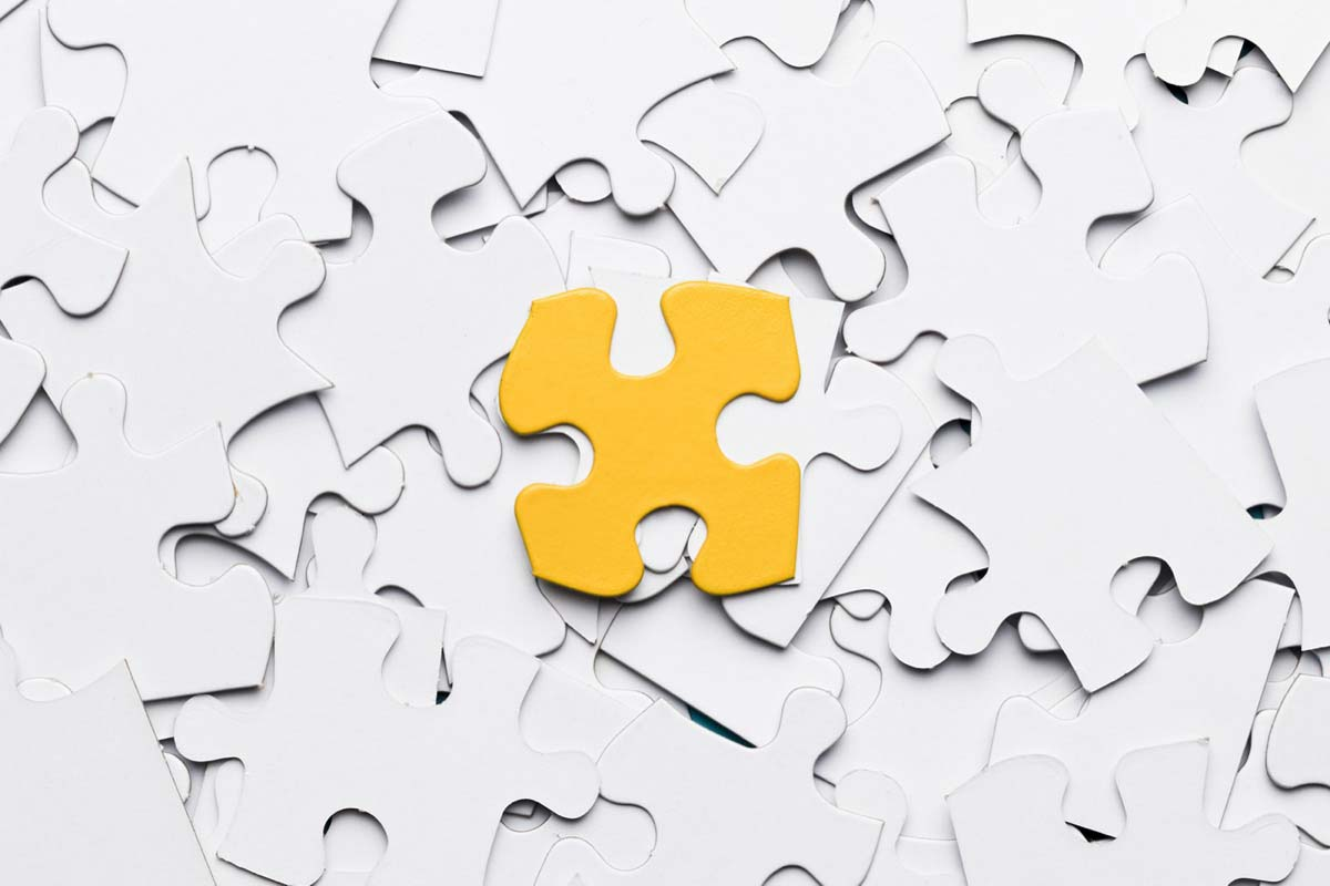 One yellow puzzle piece on a pile of white puzzle pieces