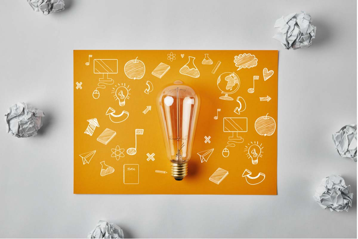 A lightbulb on top of paper with several sketches