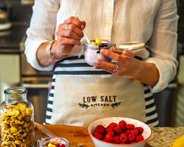 Woman in Low Salt Kitchen apron dishes out the good stuff –yolgurt parfait with granola