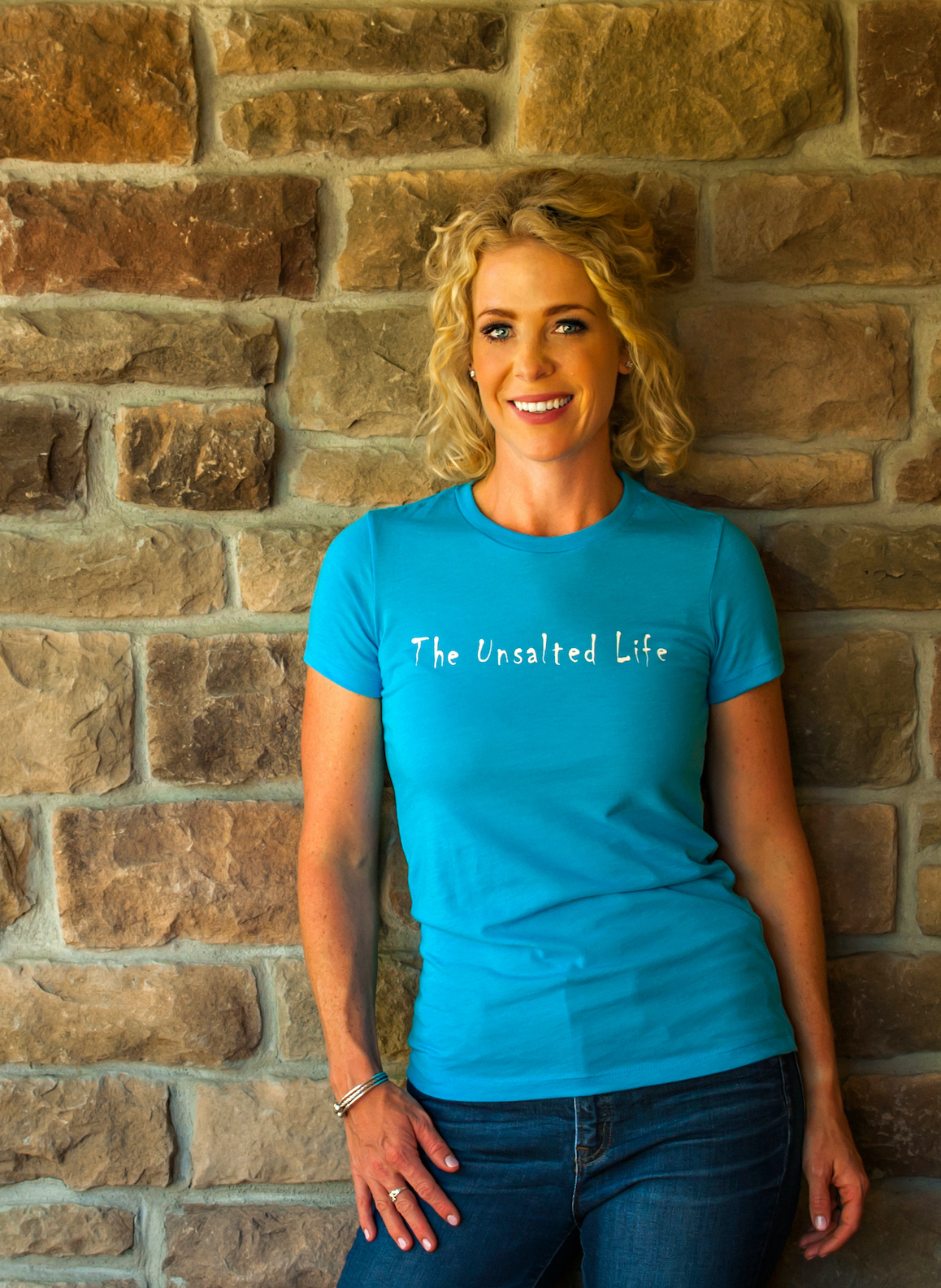 Low Salt founder Mckenzie Ellis smiling at the camera in her Unsalted Life tshirt