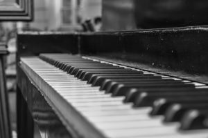 A close up black and white photo of upright piano.