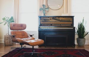 Piano in a living room behind a tan chair. Among the things to consider before moving your piano is if your new place has enough room for it.