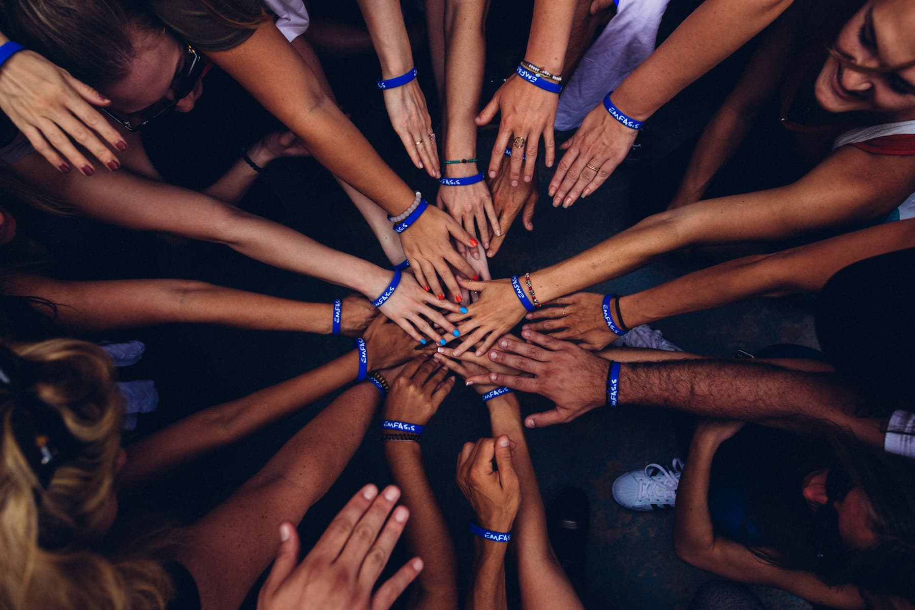 A collection of people in a circle are touching hands.