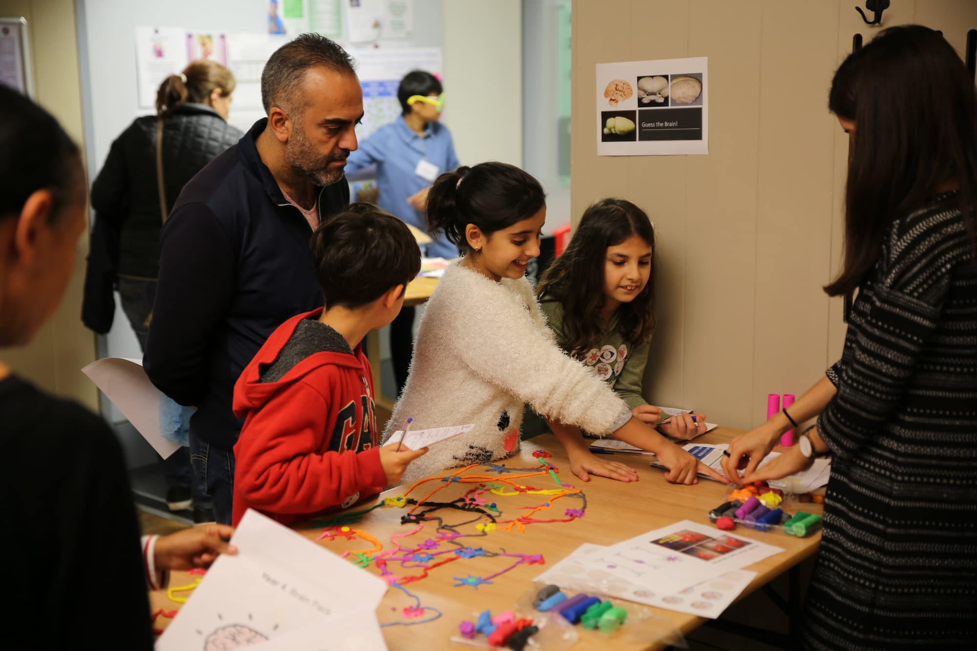 Four young people are standing around a table with a two adults looking at coloured pens and other crafting materials cleaners and having a chat.