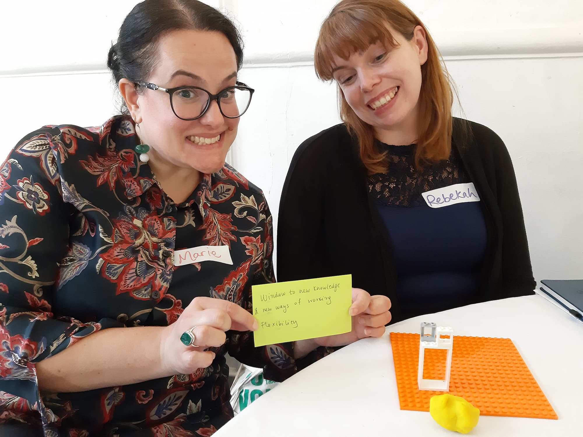 Two co-producers are sat next to each other with a colourful Lego model that they have made in front of them, one of them is holding up a post-it note that says 'Flexibility' on it.