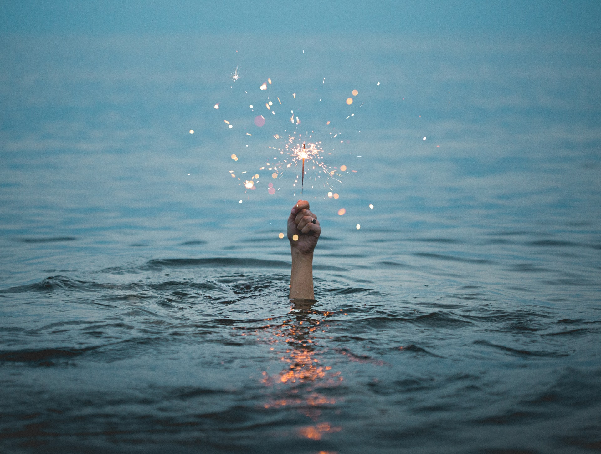 A hand is coming out of some water and is holding a sparkler which is lit.