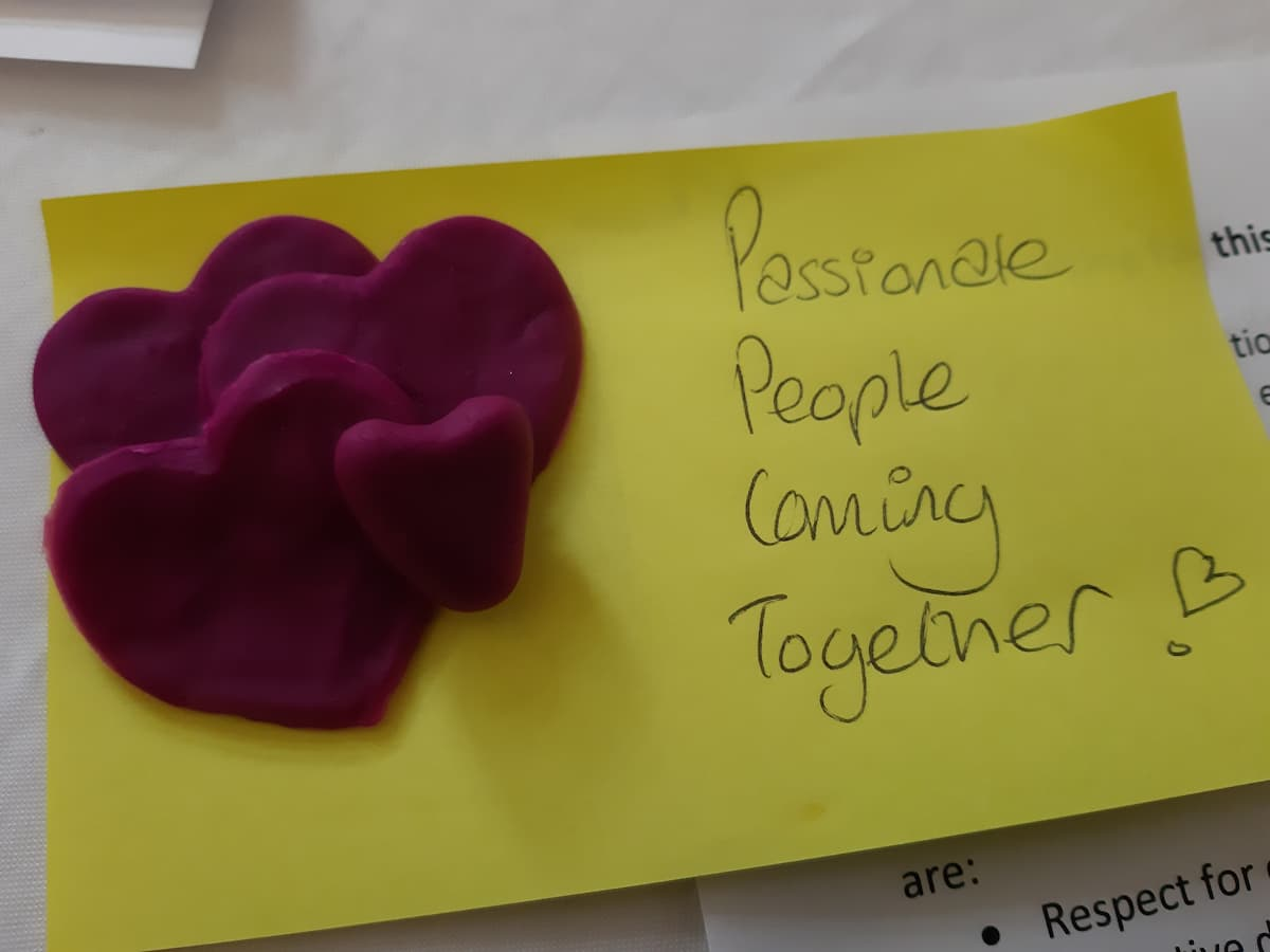 Purple play-doh hearts on a yellow post-it, with 'passionate people coming together' handwritten on it