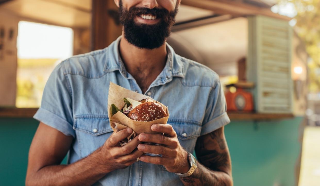 Man smiling with burger.