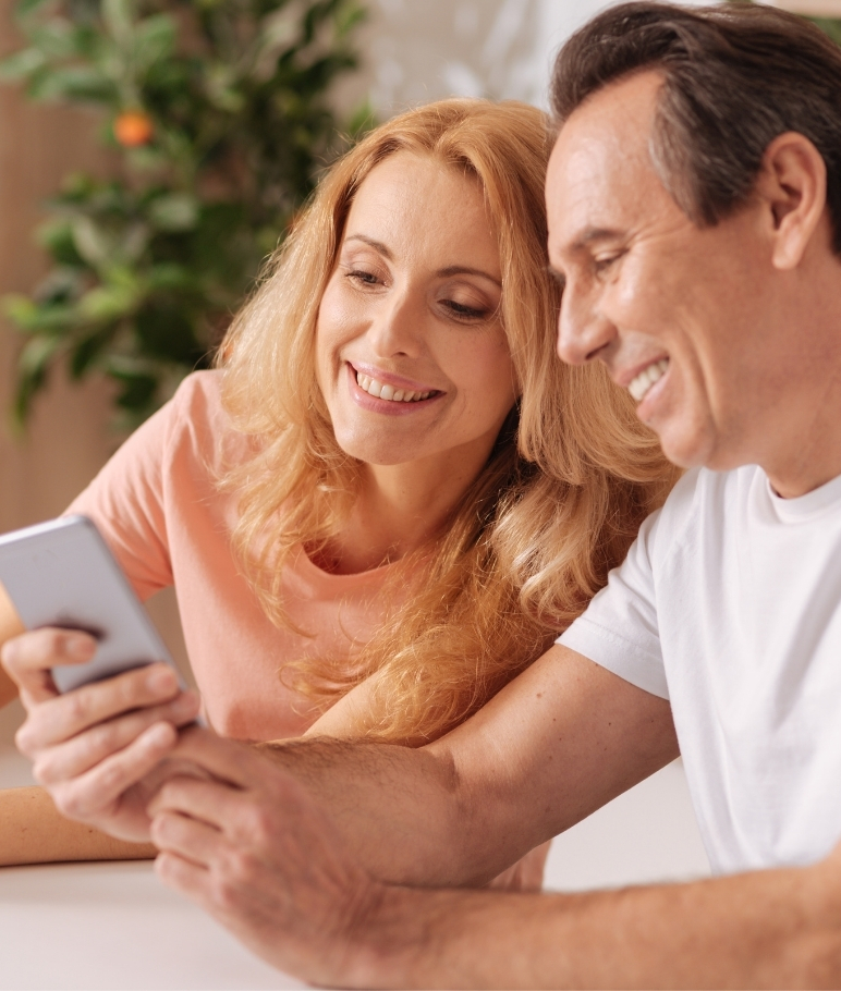 Mature couple looking at phone.