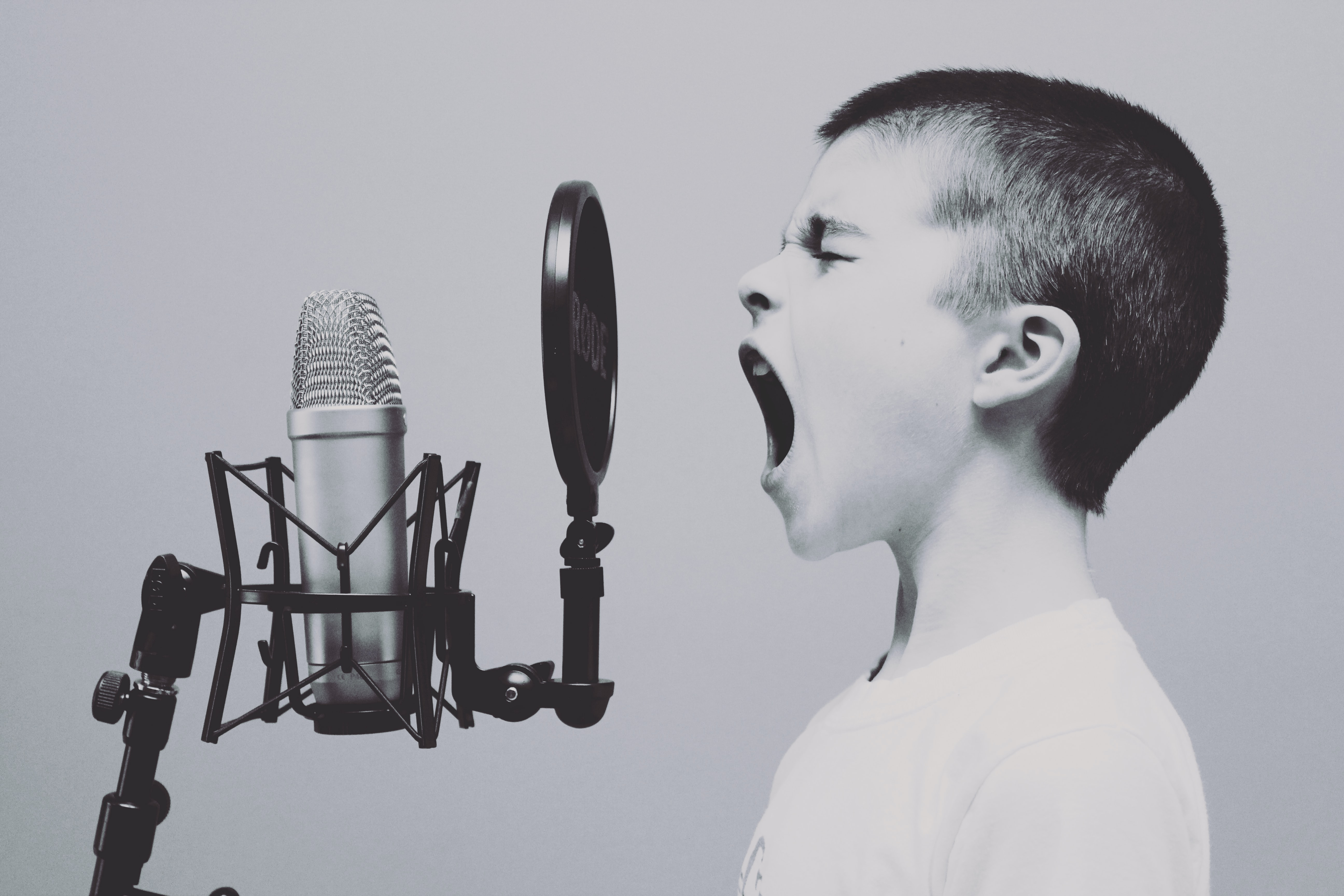 A young person shouts or sings into an old style microphone (Image credit: Jason Rosewell via Unsplash)