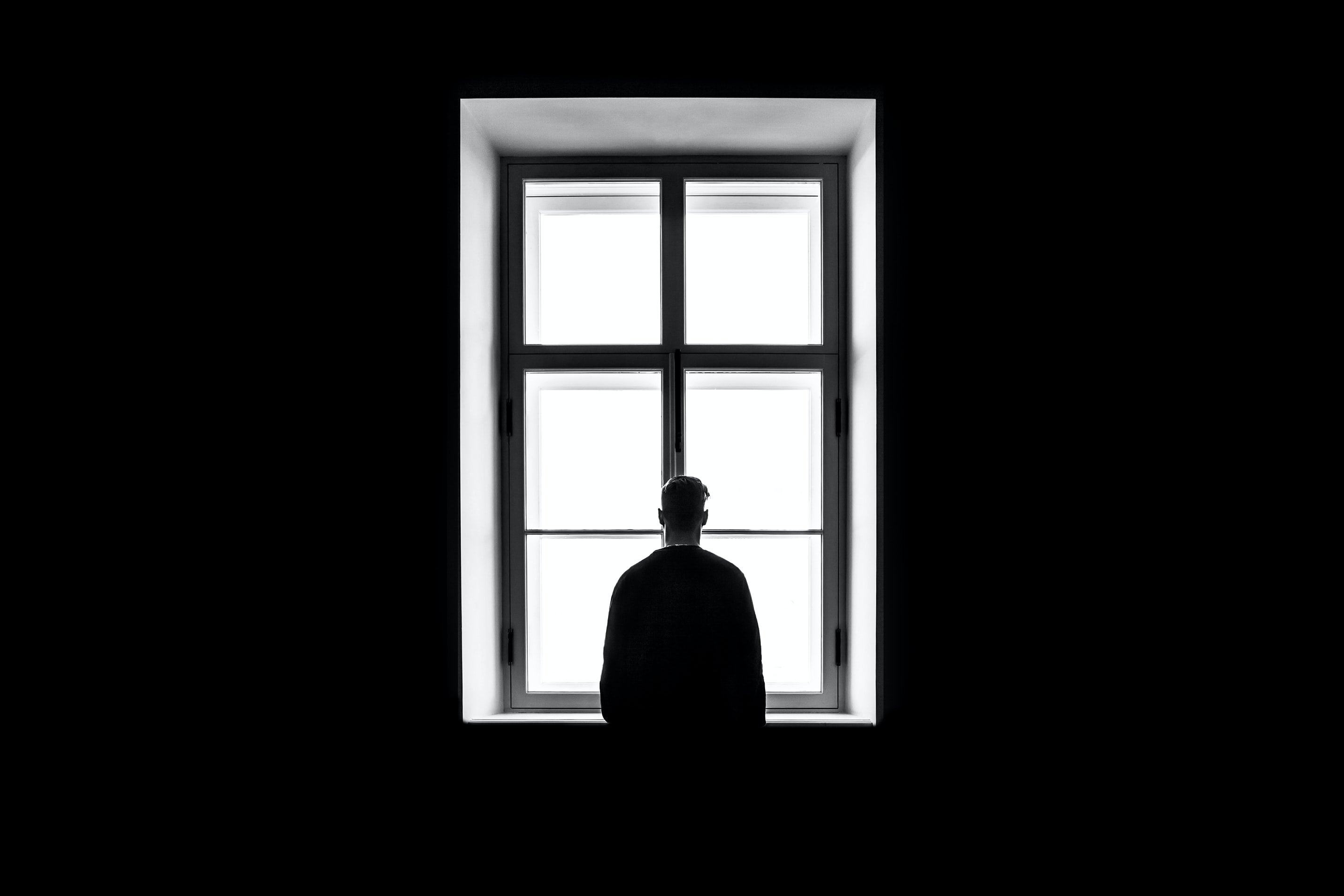 A shadowy figure stands in front of a window - all is black apart from the light from the window c.Sasha Freemind, Unsplash