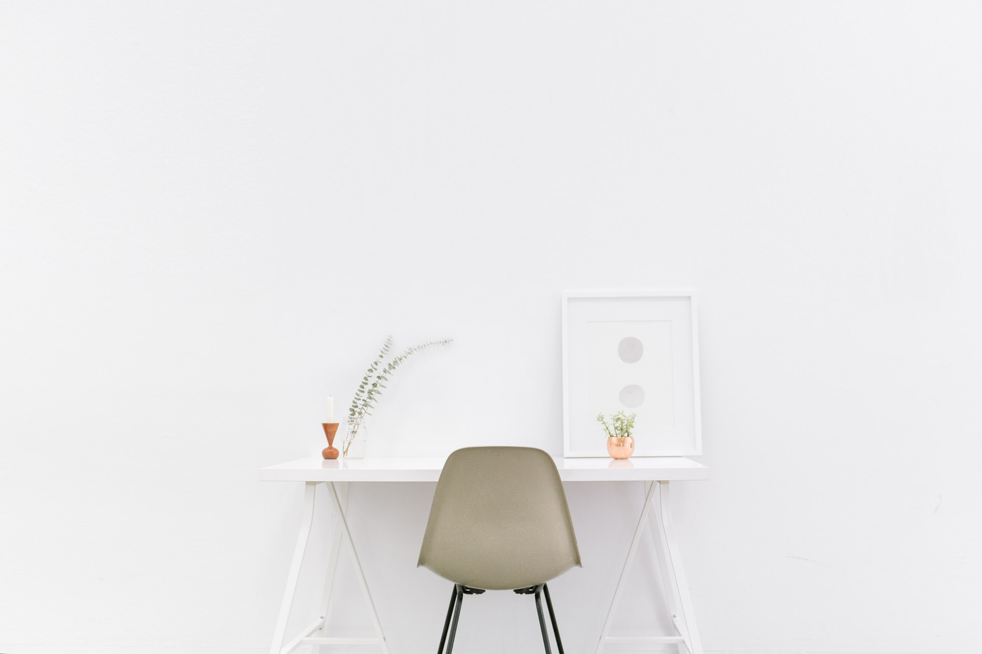An empty workspace stands in front of a white wall. A new position is ready to be filled in our team!