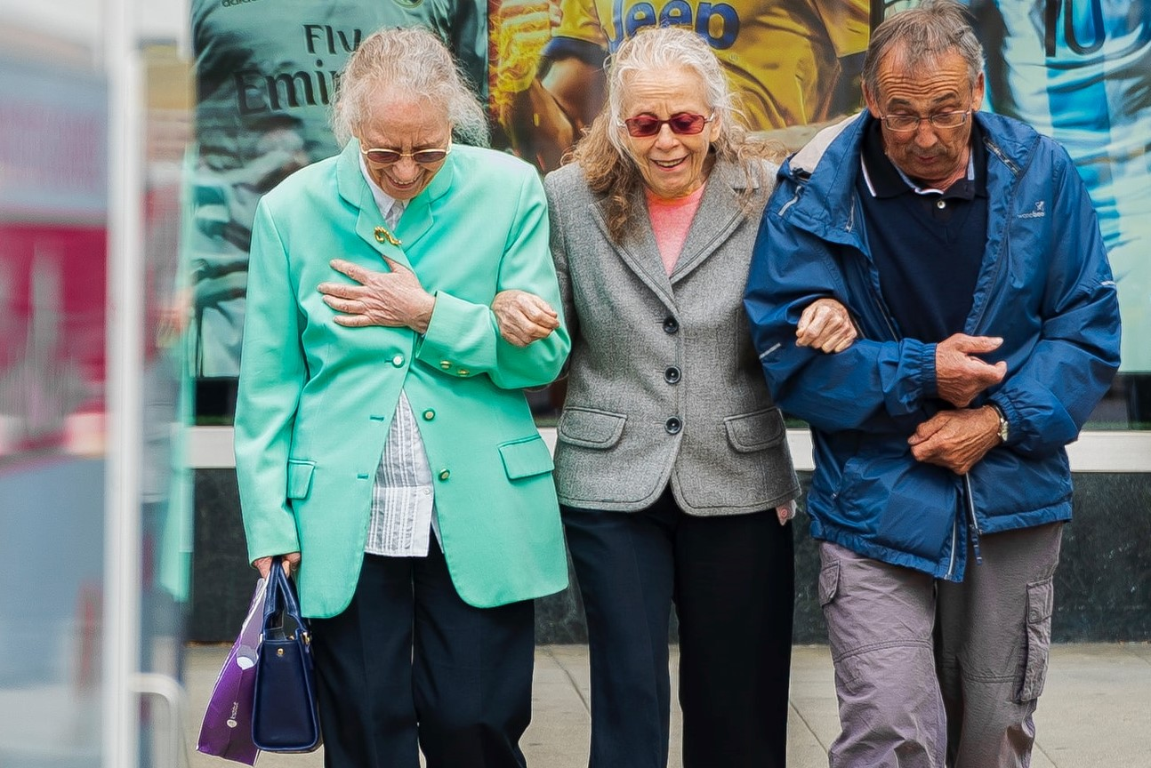 Three elderly people, arm in arm, walking on the street, wearing bright colours, and smiling.