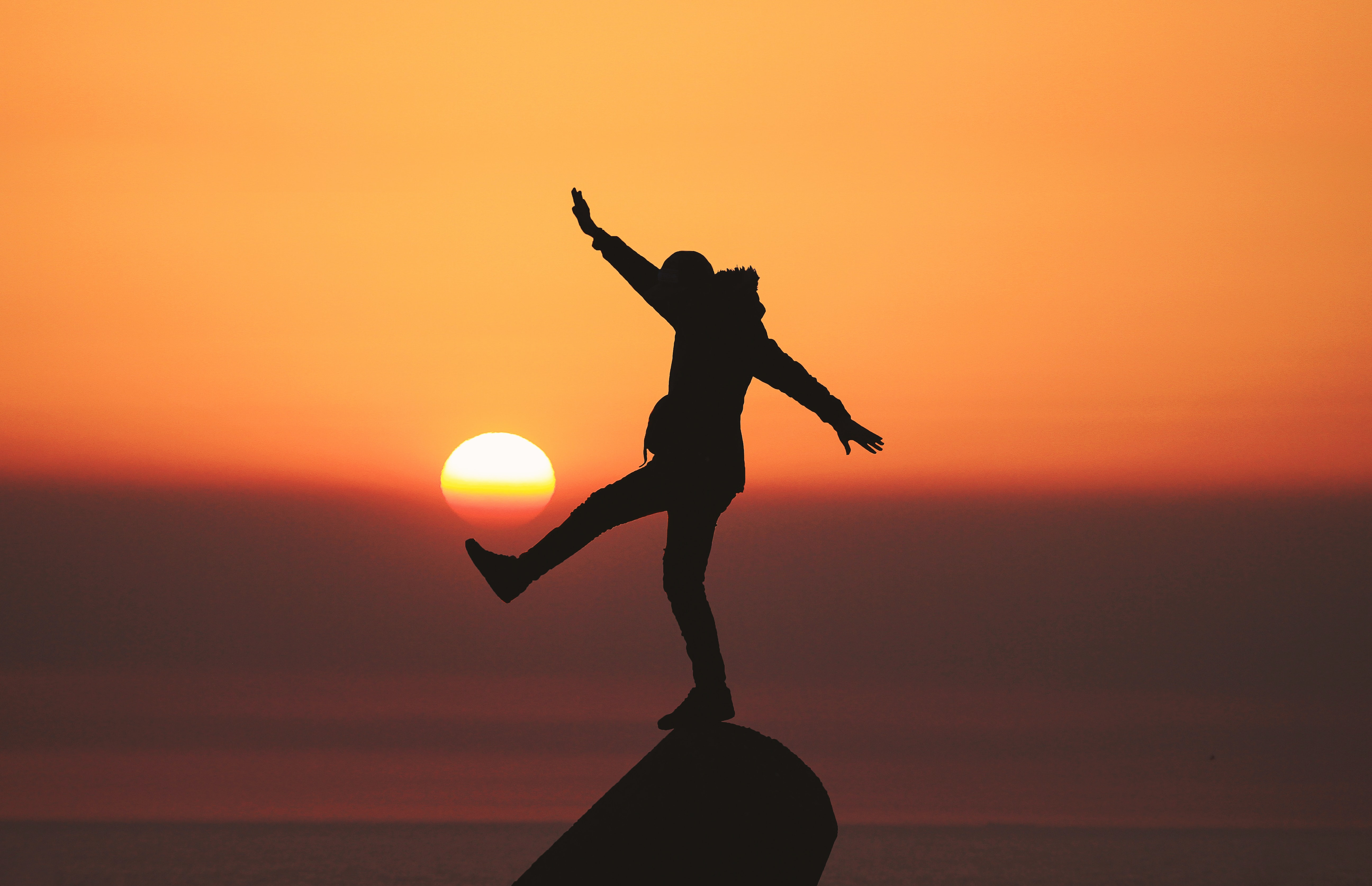 A silhouette of a person is outlined against an orange sunset - they look like they're kicking the sun. c. Aziz Achark, Unsplash