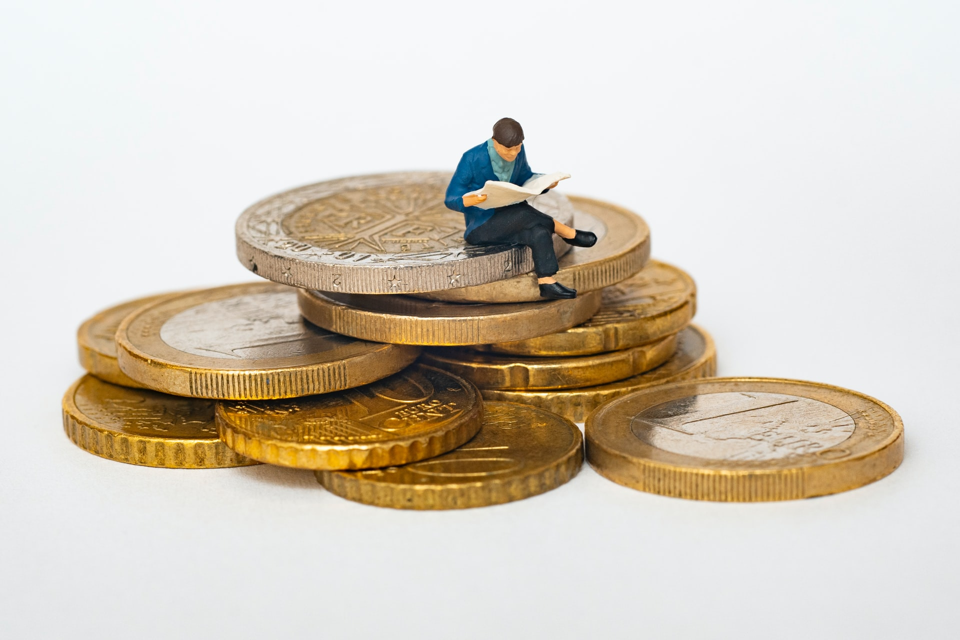 Man sitting on a pile of coins, reading a newspaper.
