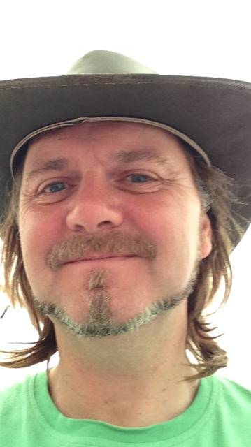 Selfie of Shaun, smiling and wearing what looks like a cowboy hat. He's wearing a bright green t-shirt.