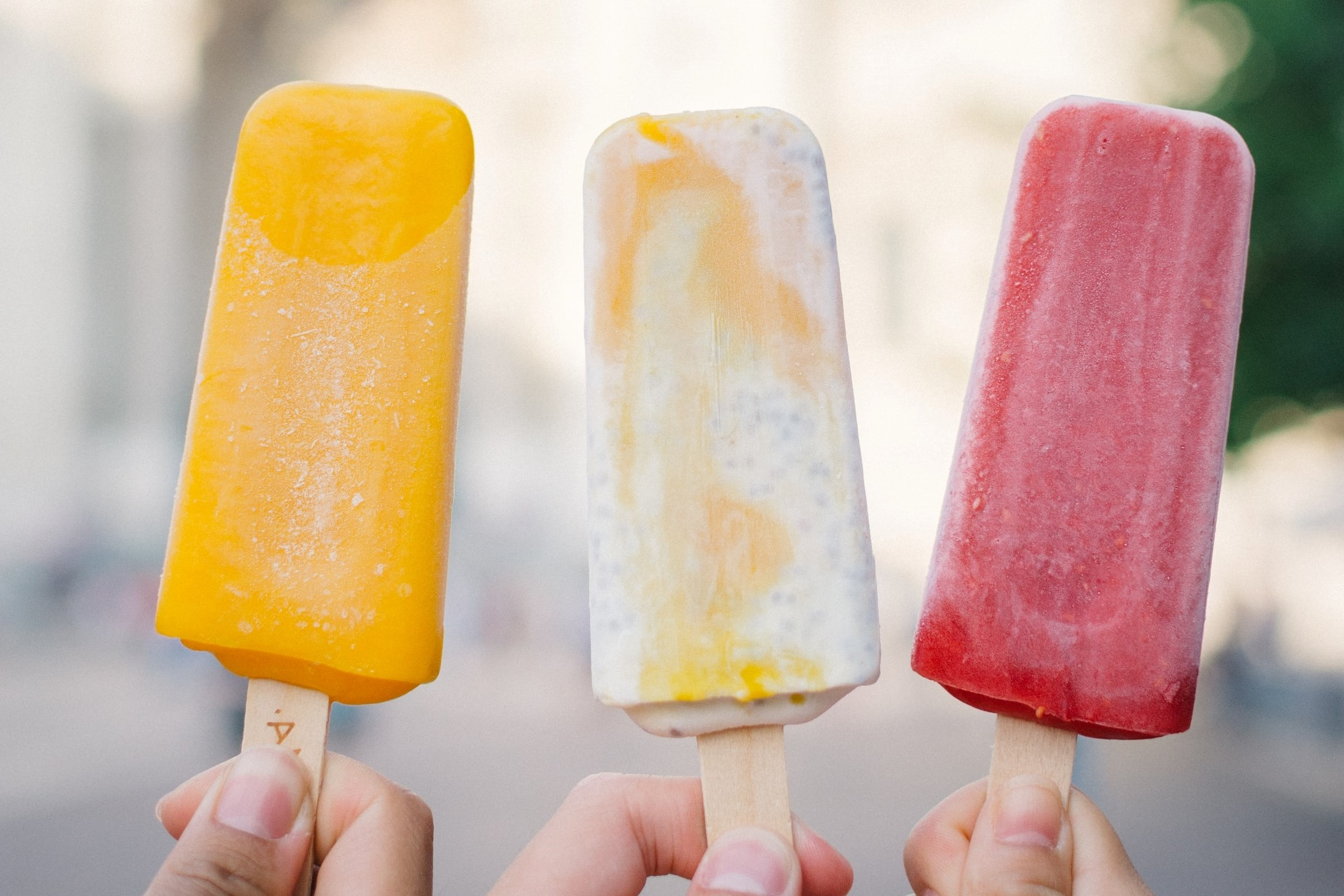 Three people hold up colourful ice lollies in the bright sunshine. One yellow, one cream, one red.