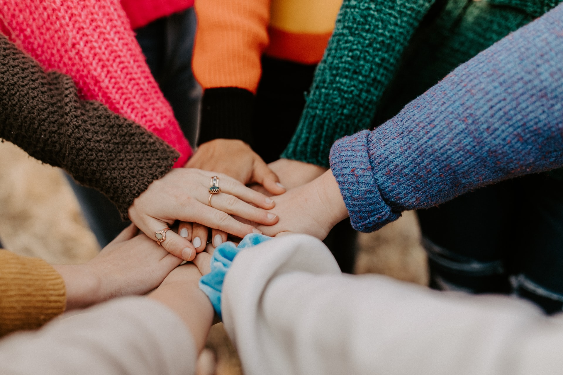 A group of people stand in a circle and reach their hands out. The hands are piled up on each other. Some are wearing rings and bracelets and the colourful sweaters and cardigans next to each other looks like a rainbow.