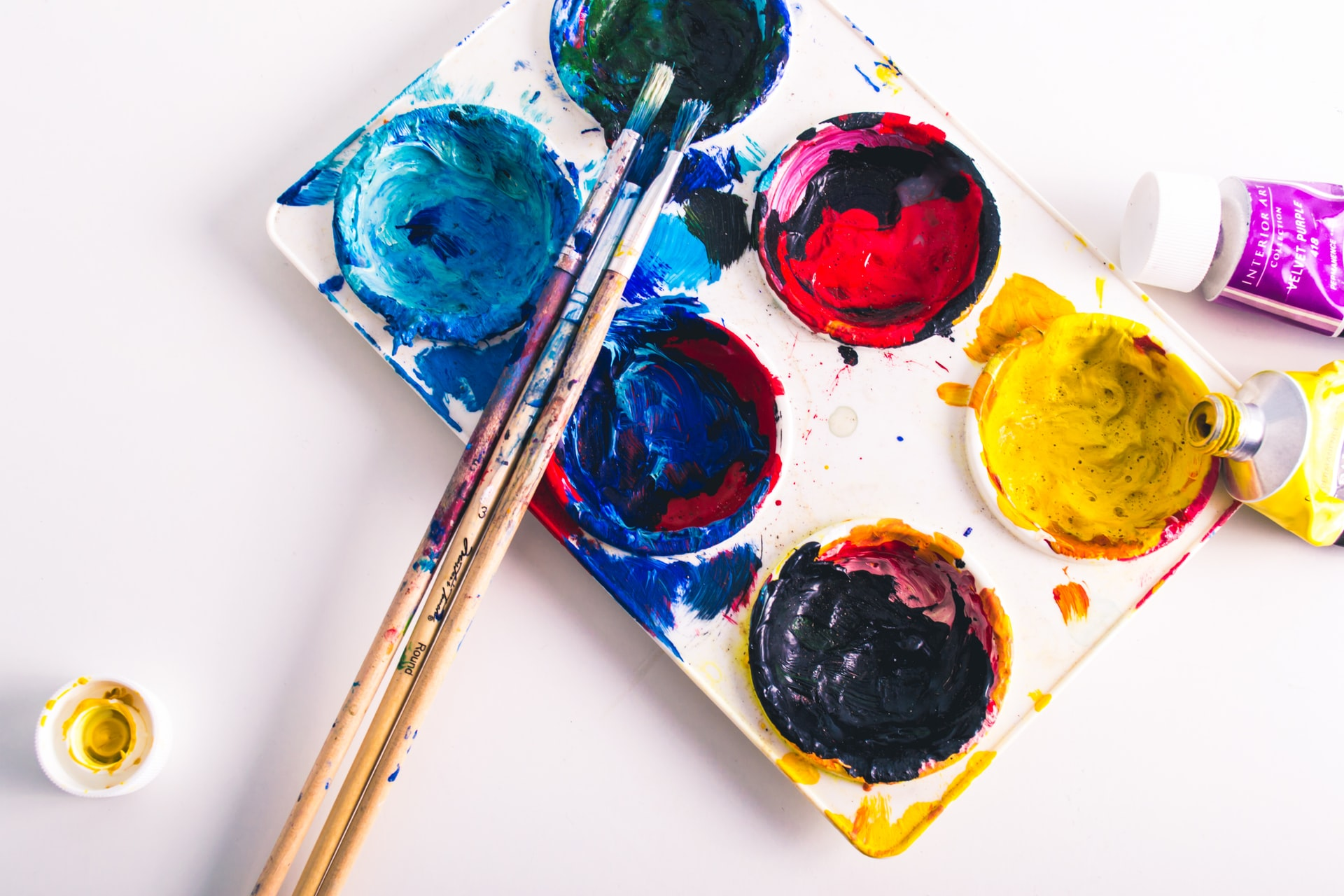 Stock photo of a paint palette with six colours: yellow, blue, navy, green, red, and brown. A paint brush lies across the palette and there's smudge of paint across the white surface.
