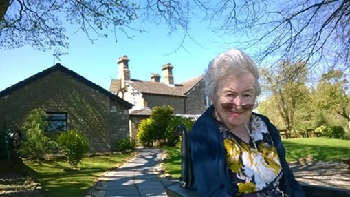 Photo of Carol, an elderly lady in front of the care home, surrounded by trees. She is wearing a navy blue cardigan and a floral blouse with pearls. She is smiling.