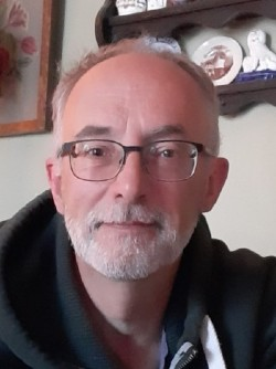 A photo of Nick, showing his face and shoulders. He's wearing a pair of glasses and a dark hoodie. Nick also has a beard.