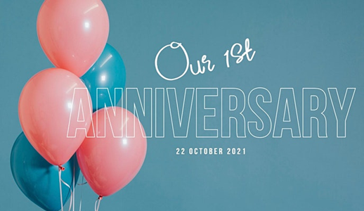 Green and pink balloons sit next to the words 'Our first anniversary 22 October 2021' in white writing, against a turquoise background