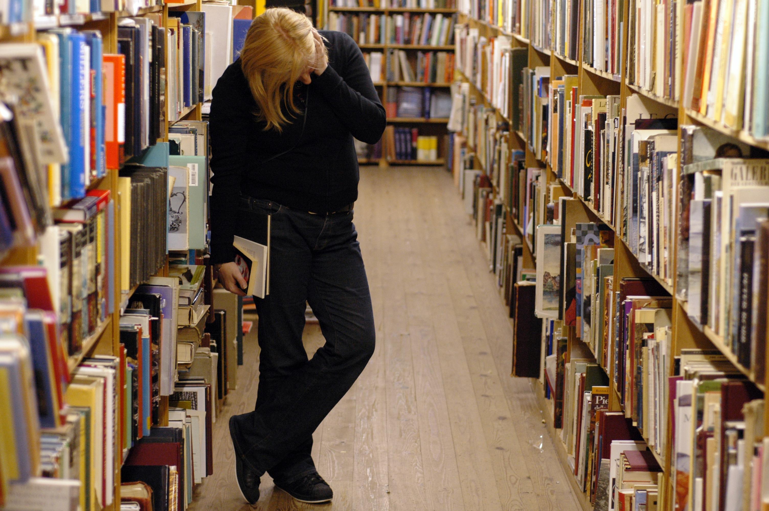 Frau stöbert in einer Bibliothek.