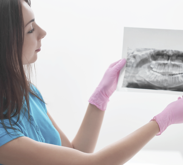 A dentist looking at an x-ray of teeth