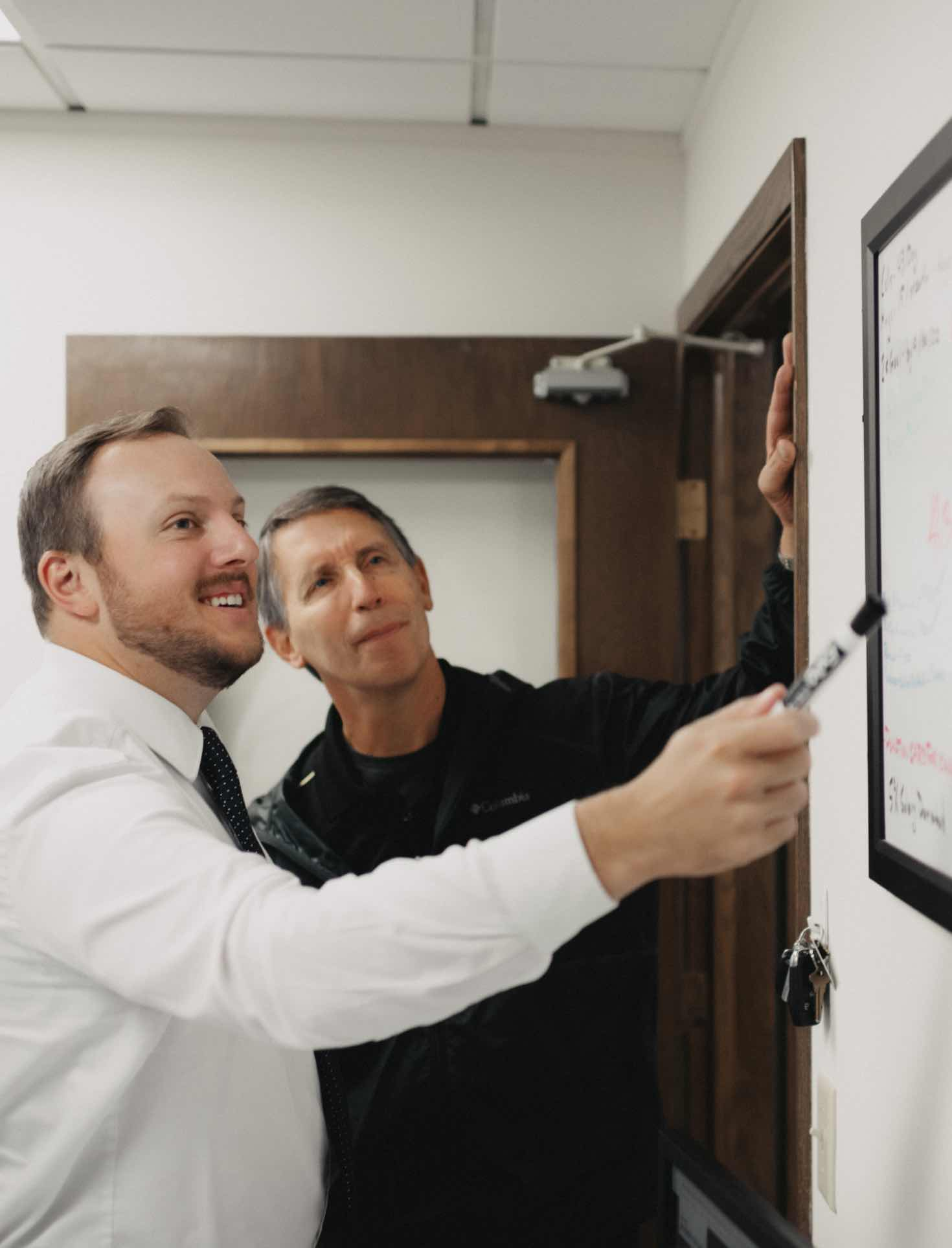 Photo of two team members looking at a whiteboard
