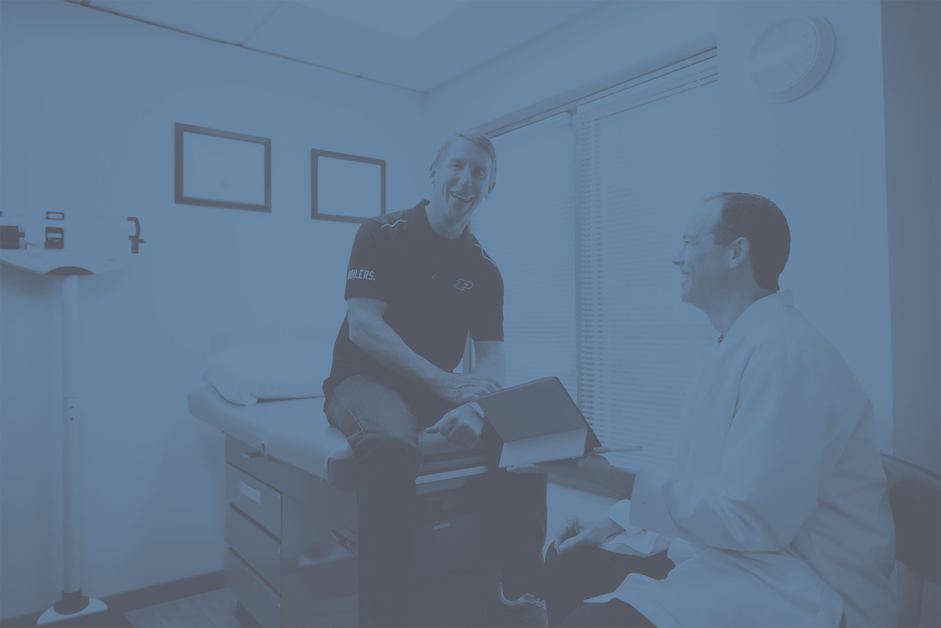 Photo of Dr. Kloess talking with a patient