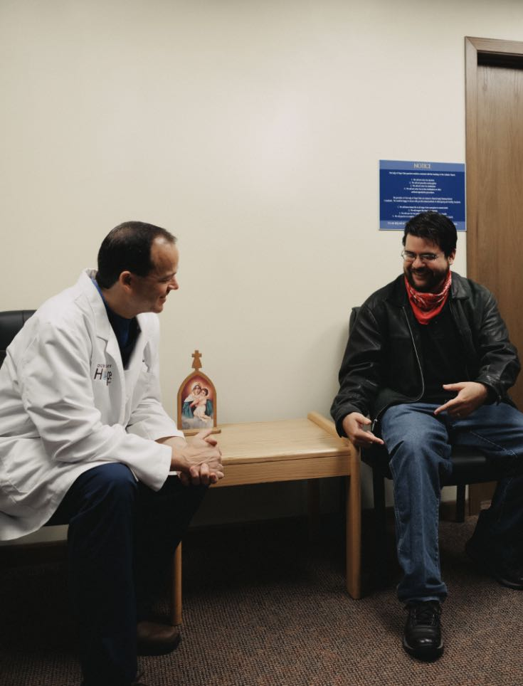 Photo of Dr. Kloess sitting down next to a patient having a conversation