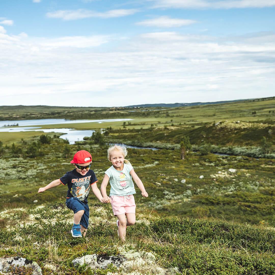 Liten gutt og jente på fjelltur som løper mot kamera