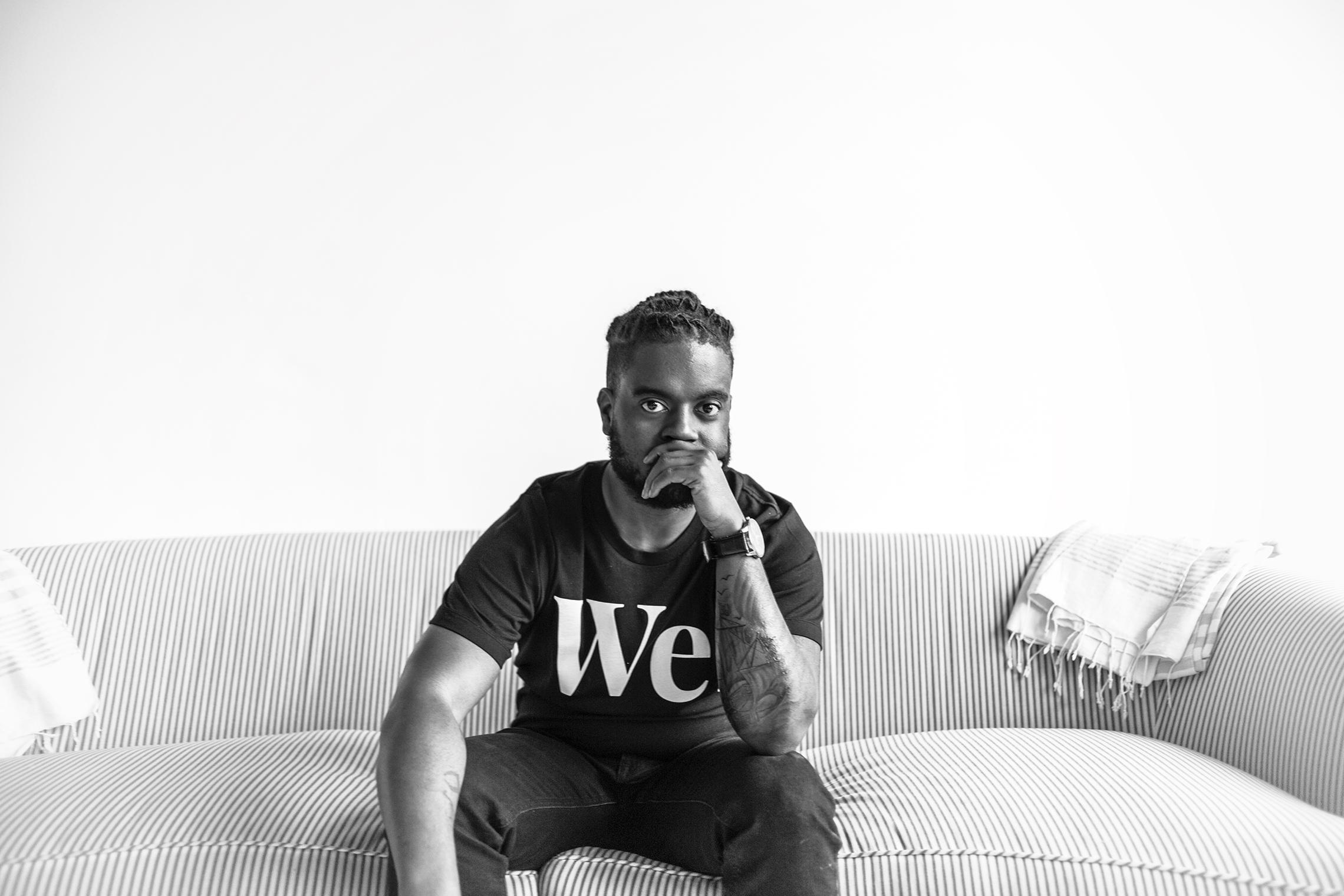 """Kareem Manuel poses while wearing a """"We"""" shirt."""