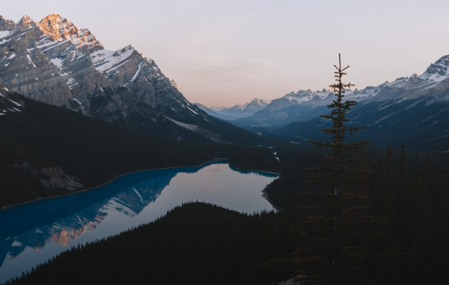 A landscape photo of a lake surrounded by mountains