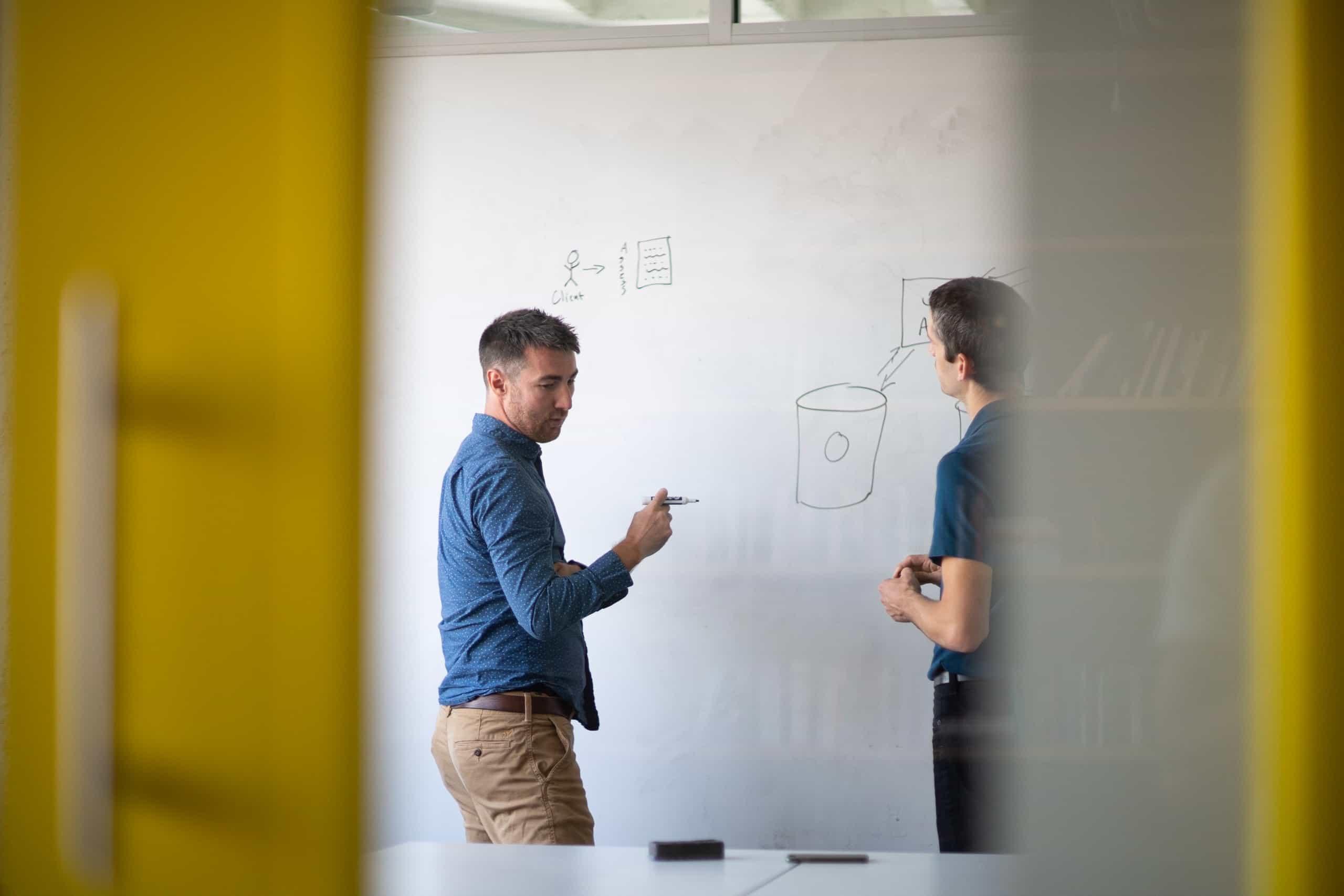 Medium shot of Luke Golden and Matt Campbell, Whiteboard employees, conferring in front of a whiteboard.