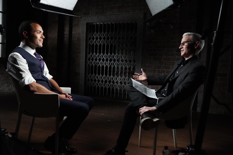 Medium shot of Anderson Cooper talking with Alexander McLean.