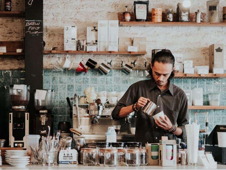 A barista prepares a latte.