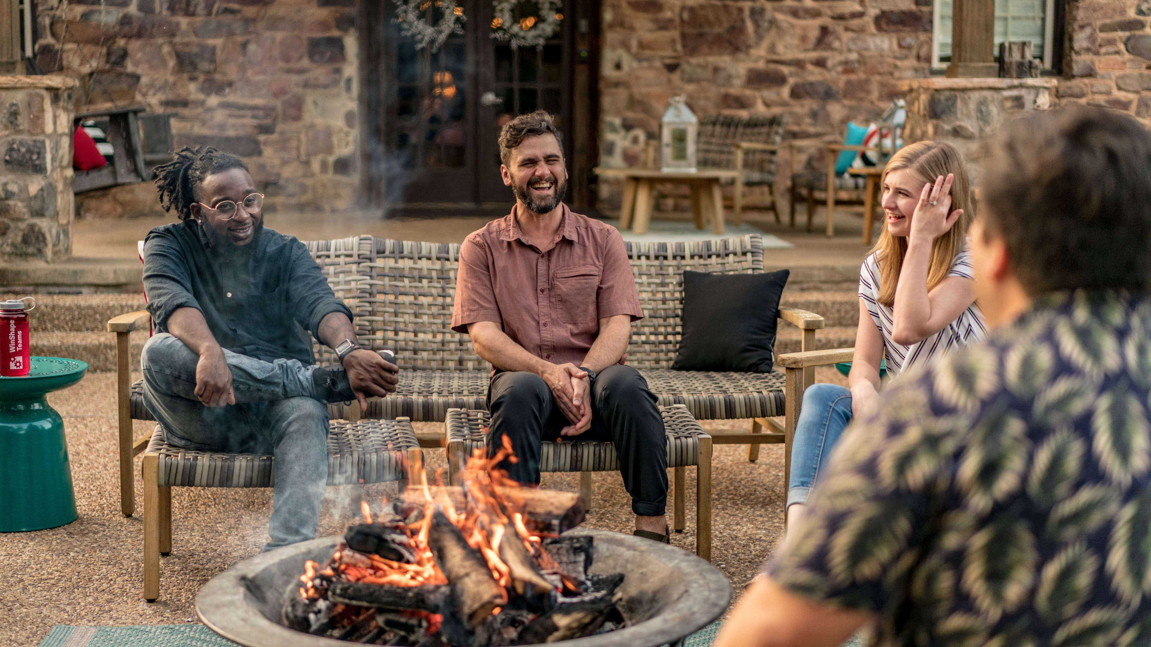 At a Winshape gathering, a group of attendees chat while gathered around a fire.