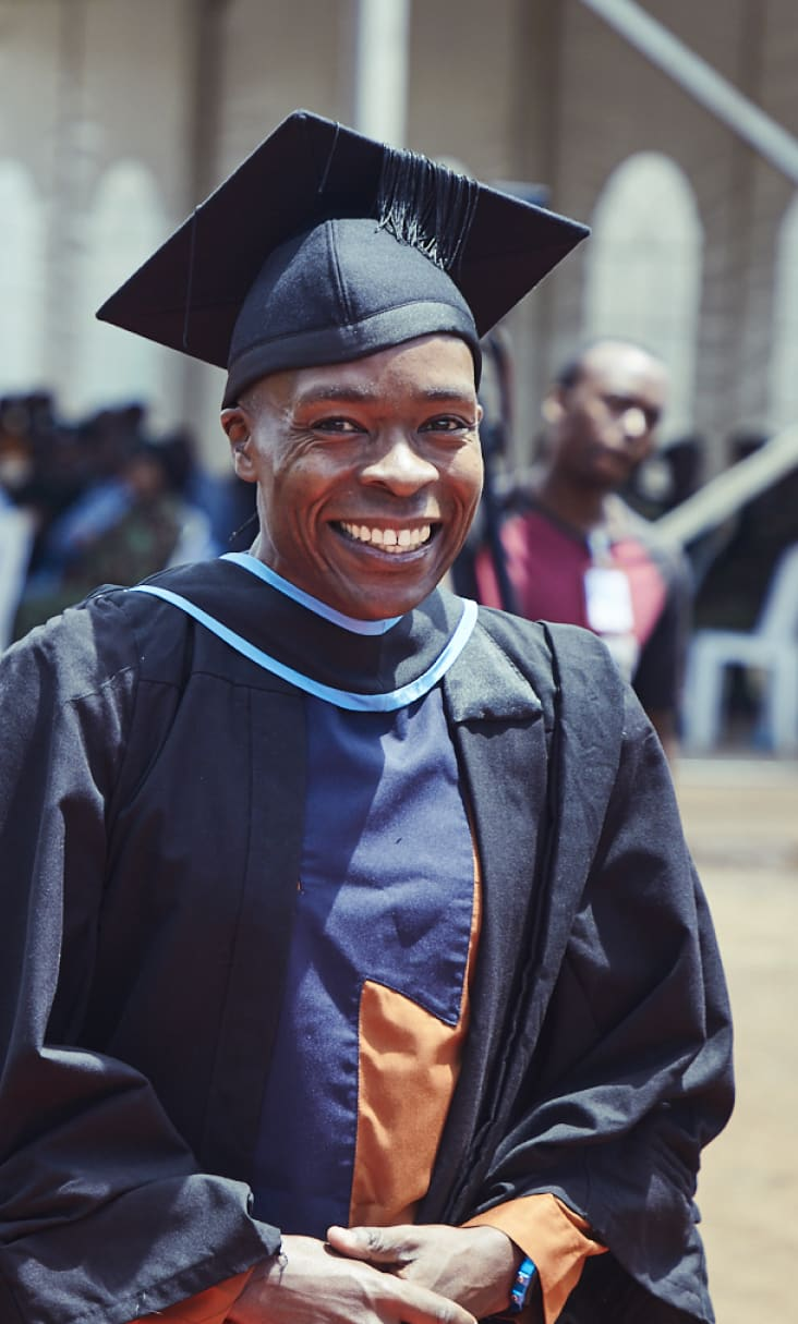 A Justice Defenders graduate walks in his robe, holding his diploma.