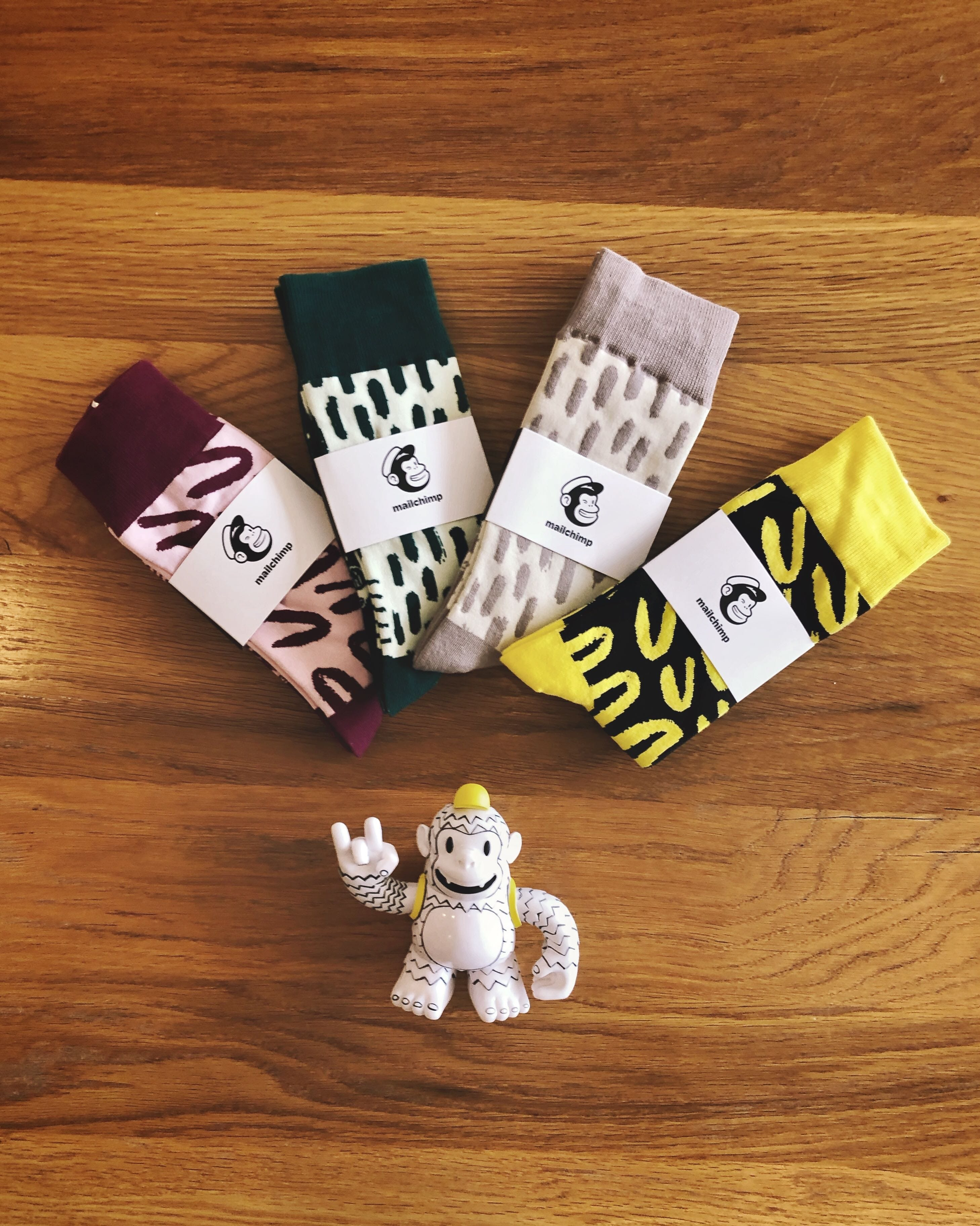 An assortment of Mailchimp swag including socks and a monkey.