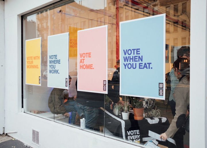 "Storefront with posters that read ""Vote when you eat"" and ""Vote where you work."""