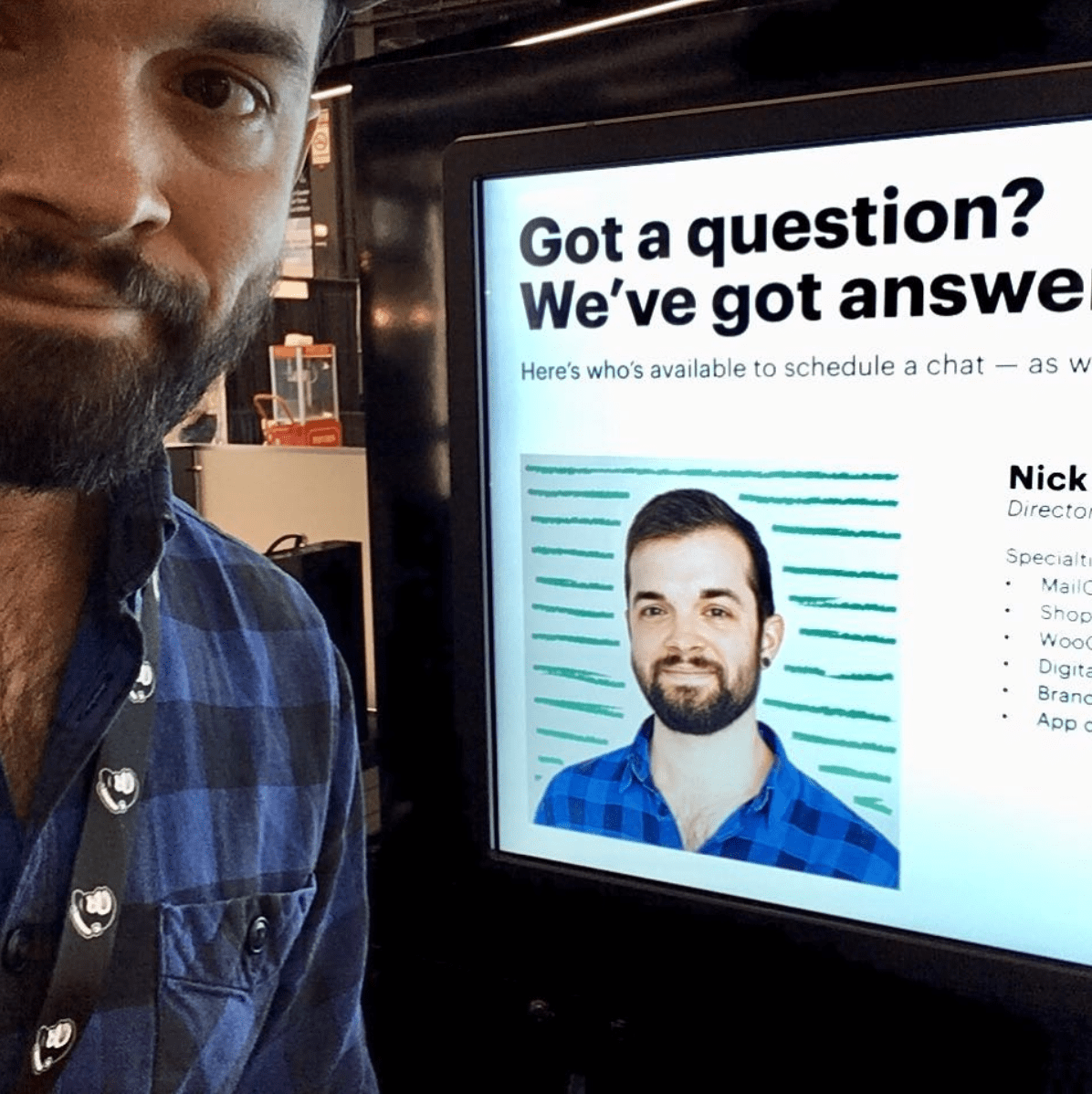 Nick Blackmon posing in front of a computer showing an article featuring his work with Mailchimp.
