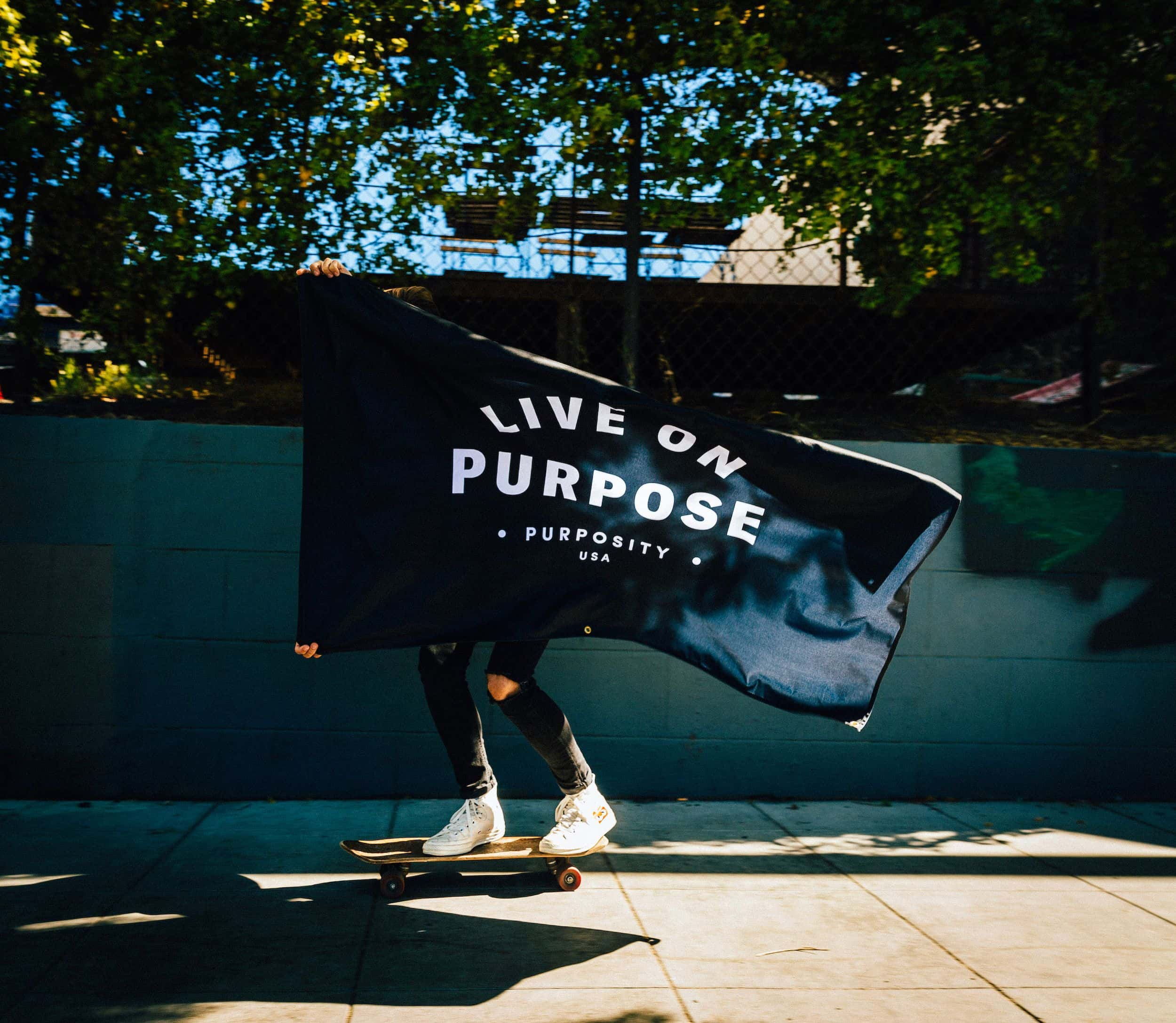 """A woman displays a flag reading """"Live on Purpose - Purposity""""."""