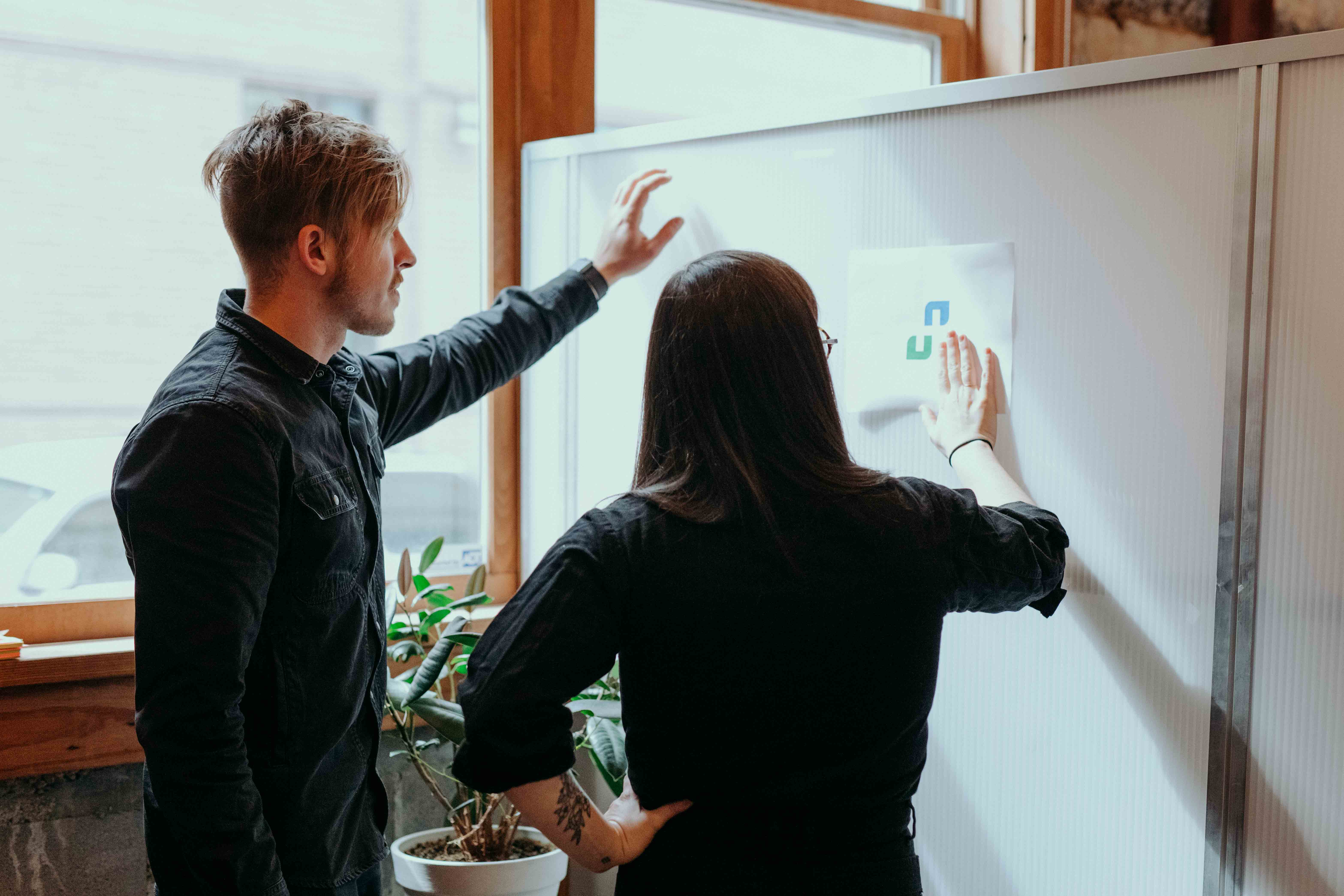 Kody Dahl and Katie Cooper, whiteboard employees, brainstorm in front of a whiteboard.